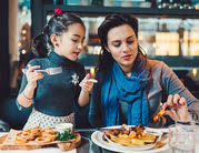 mom and daughter eating at restaurant