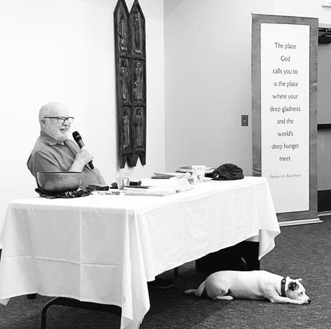 Richard Rohr seated at table with his dog Opie by his feet