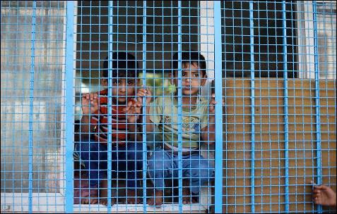 Dos muchachos palestinos, que huyeron la casa de su familia antes de la ofensiva terrestre israelí, miran por la ventana del aula de la escuela Naciones Unidas-run en Rafah, en el sur de la Franja de Gaza.