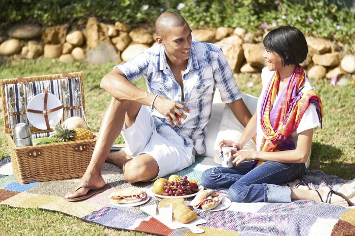 Photo of couple enjoying food during a picnic.