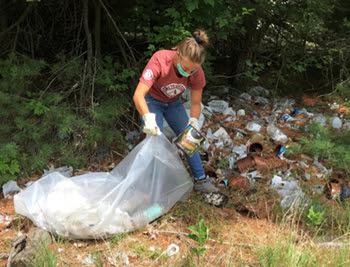 female volunteer in face mask picks up garbage in forest