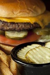 Una hamburguesa con queso al lado de un cuenco que contiene pepinos encurtidos. Enlace a la información en inglés sobre la foto