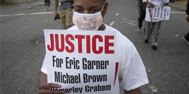 Uno de los participantes en la manifestación de este sábado contra la brutalidad policial y por la muerte de Eric Garner en Staten Island, Nueva York. REUTERS/Carlo Allegri