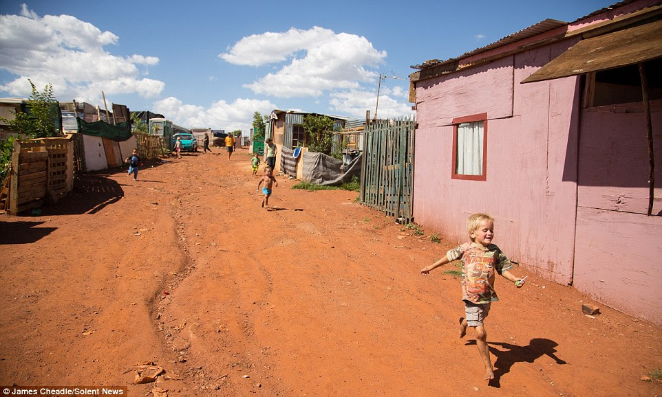 Children run along the rocky, arid ground at the camp - they were born after the end of apartheid in 1994