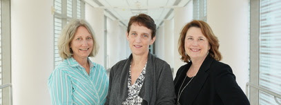Karen Baker, Dr. Colleen Hadigan and Victoria Anderson stand in a hallway