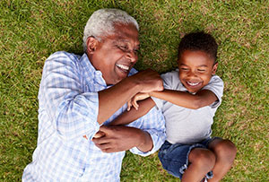 Grandfather and grandson playing on grass