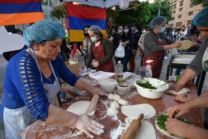 Des femmes, qui ont fui le Haut-Karabakh, confectionnent des pains, à Erevan, le 26 octobre. Les recettes de ces ventes sont destinées à soutenir les populations de l'enclave.