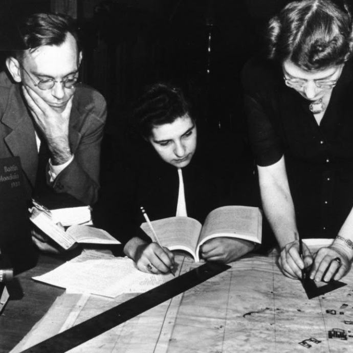 Photograph of Bill Burke, Jane Mull, and Gladys Hamlin preparing a map at the Frick Art Reference Library