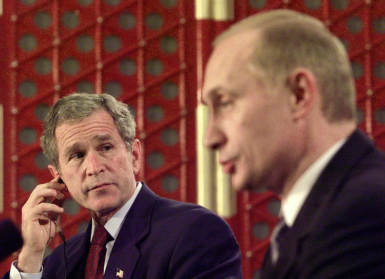 George W. Bush listens to Putin in Shanghai. (Tim Sloan/AFP) </p>