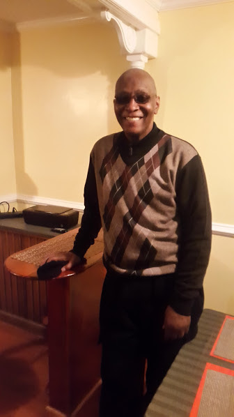 A man in a sweater, slacks and shades poses and smiles in a room with cream walls and white molding.