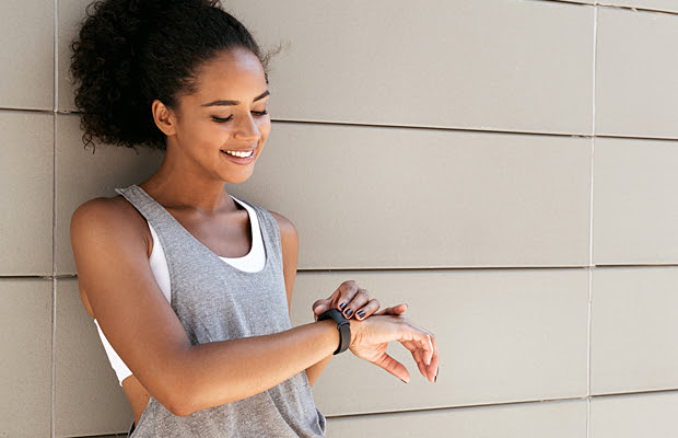 A woman looking at the fitness tracker on her wrist.