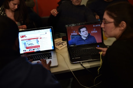 Activists watch an interview with Syriza leader Alexis Tsipras newspaper at the party's election centre in Athens last week.