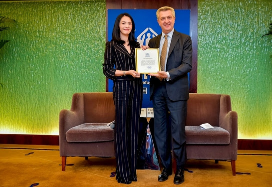 Filippo Grande presents a certificate of renewal to UNHCR Goodwill Ambassador Yao Chen