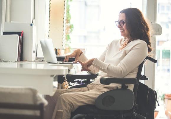 Mujer en silla de ruedas trabajando detrás de un ordenador sonriendo