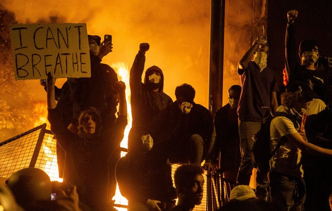 A photo of rioters in masks holding signs as a city burns