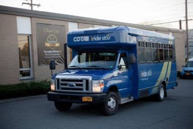 Blue bus outside of a building