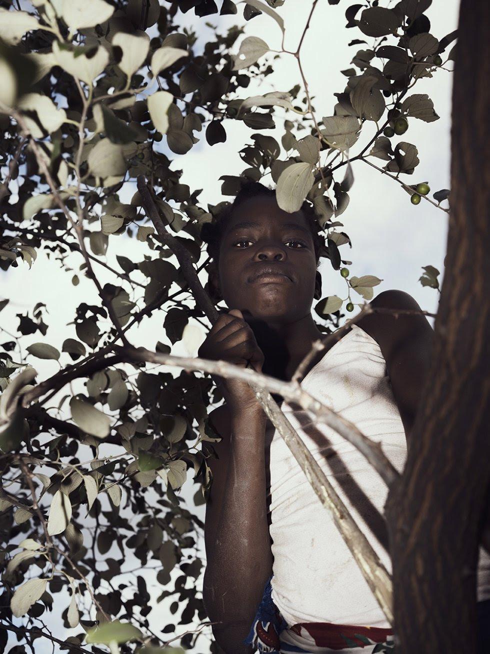 El polvo causa graves problemas de salud a los residentes, pues desde hace tiempo han empezado a producirse conflictos en la zona como resultado de la contaminación y del acaparamiento de tierras y aguas. Un niño recolecta fruta en uno de los pocos árboles encontrados en los muchos pueblos de Moatize.rn