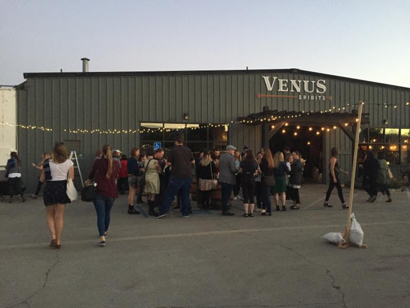 The facade of Venus Spirits, filled with people and lights out front.