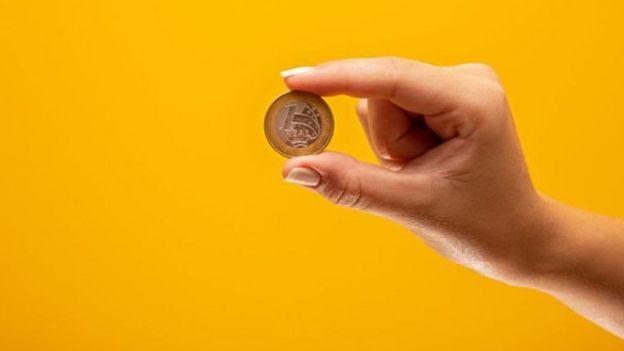 Mão segurando moeda