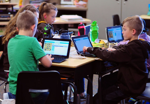 Fourth-grade students sit around a table, each playing a game on a laptop that teaches them to code.