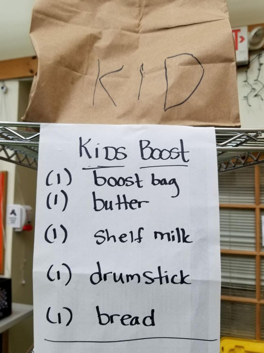 Paper grocery bag and sign that reads Kids Boost_ 1 boost bag_ 1 butter_ 1 shelf milk_ 1 drumstick_ 1 bread