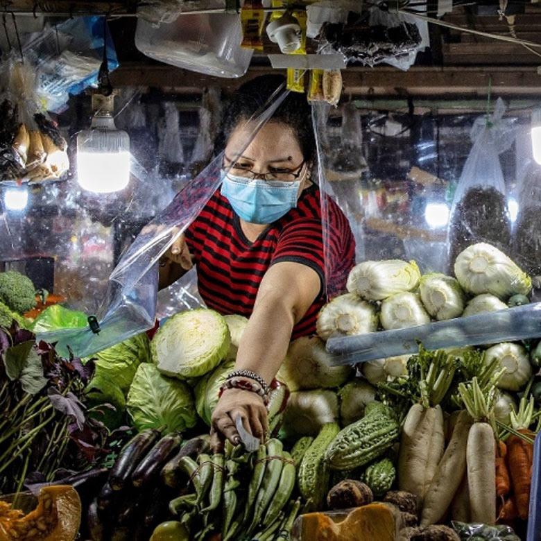 Una vendedora detrás de una lámina de plástico en su puesto ubicado en un mercado de Las Pinas, la zona metropolitana de Manila (Filipinas). Fotografía: © Banco Mundial.