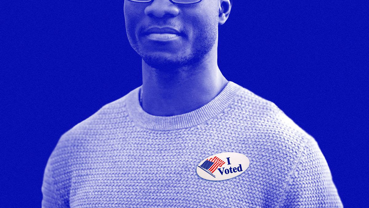A masculine black person in a sweater with an 'I Voted' sticker