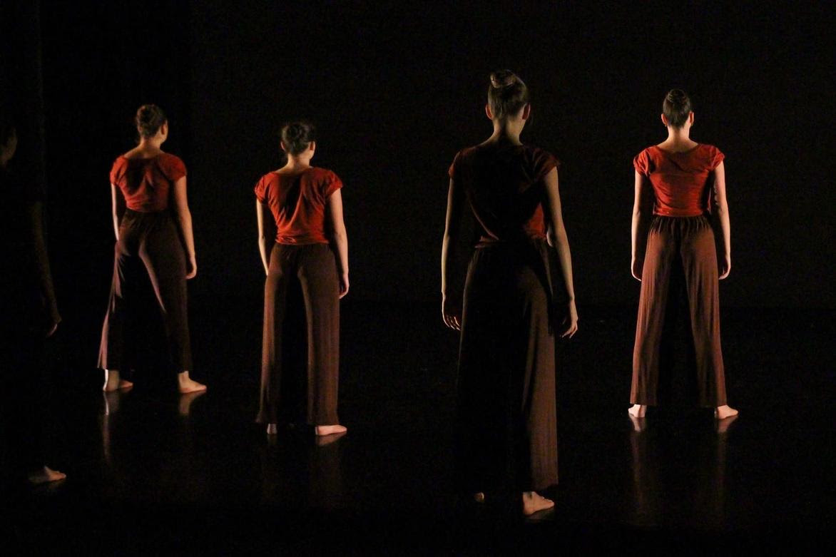 Four dancers stand with backs to the camera in dramatic darkness