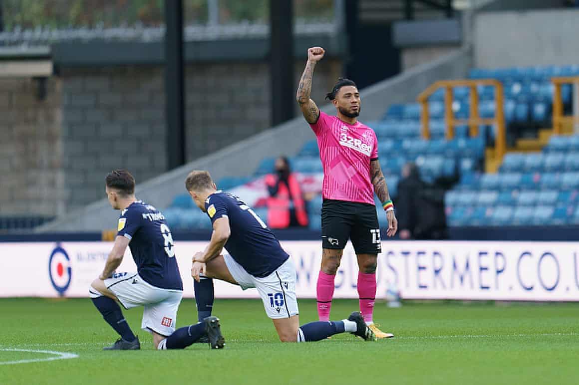 Millwall players take a knee as Colin Kazim-Richards raises his fist.
