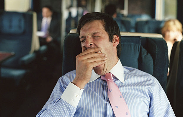 A man yawning on a train.