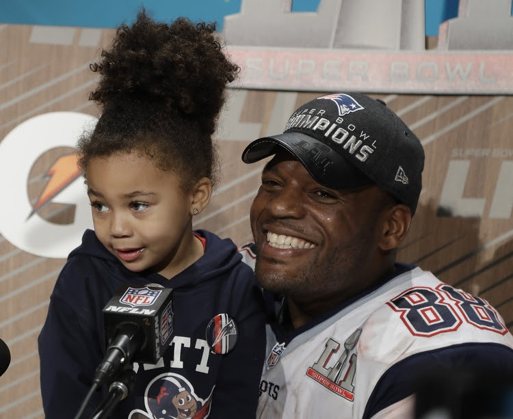 Martellus Bennett, with his daughter, answers questions after the Super Bowl in Houston last night. He said he will boycott the White House ceremony to recognize the team's championship because he objects to Donald Trump. (Chuck Burton/AP)</p>