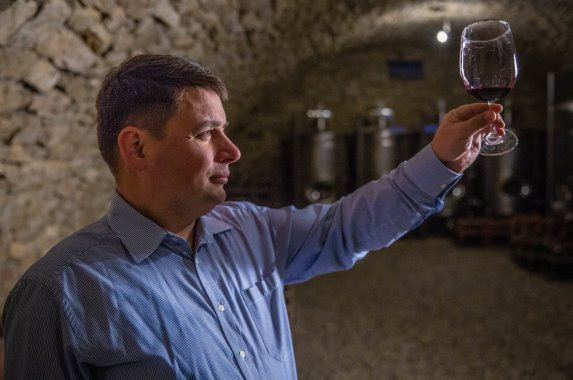 an holding up wine glass containing dark liquid (Colby Gottert for USAID)