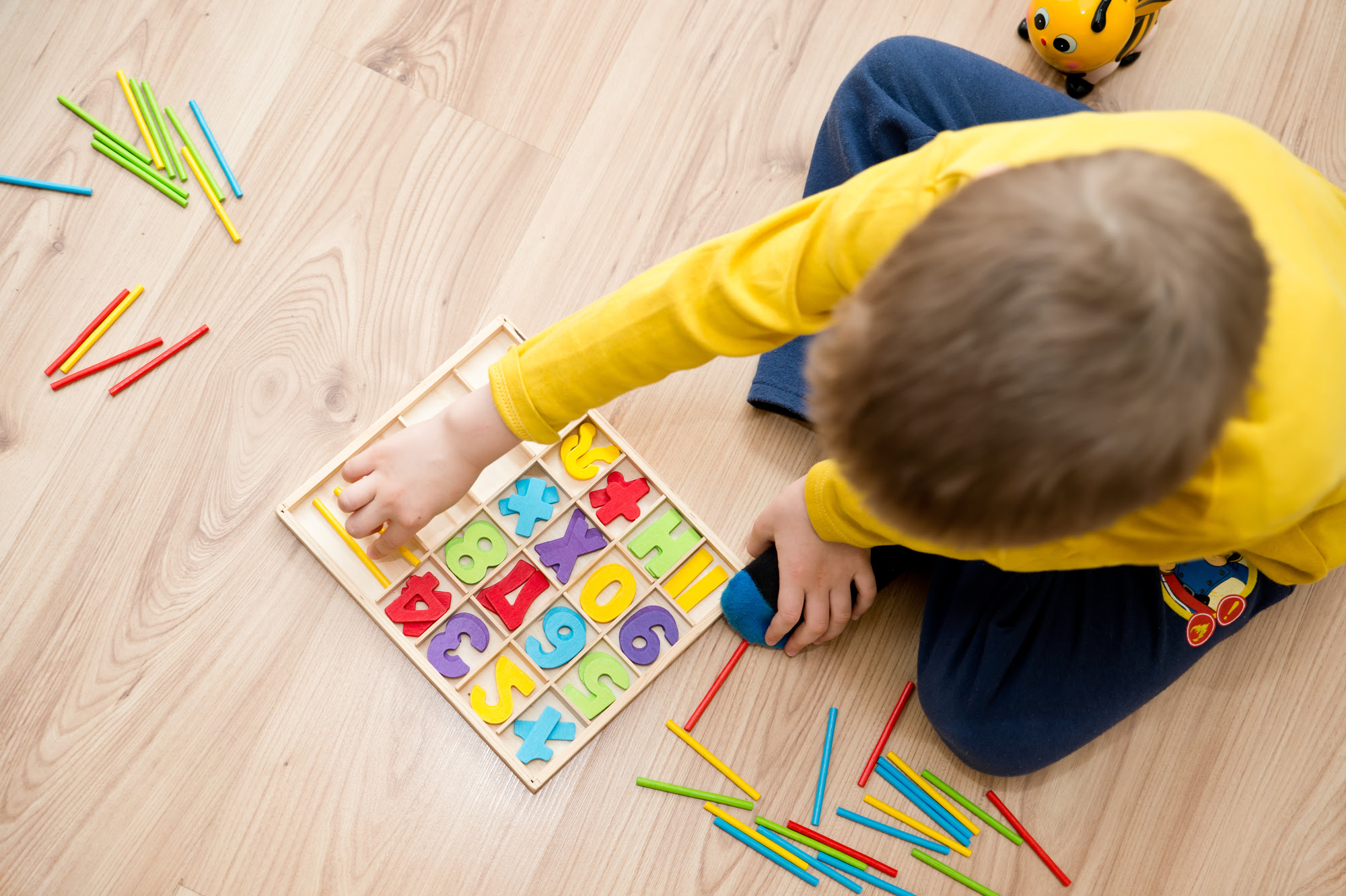 A little boy playing with a colorful counting number set on the floor.