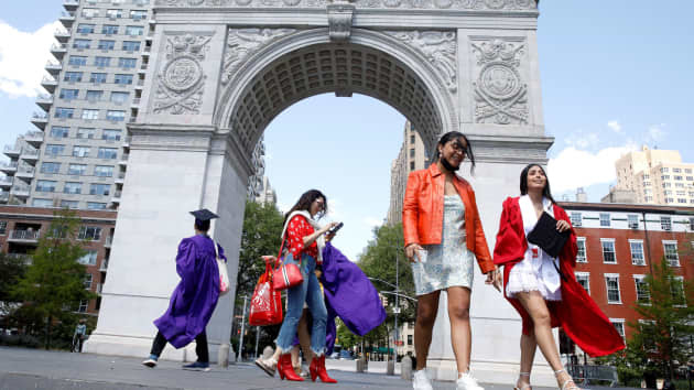 Students walk in the Washington Square Arch without masks
