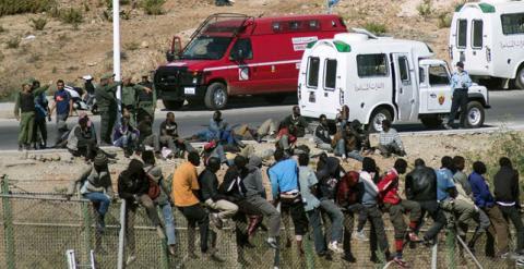 Inmigrantes subsaharianos encaramados en la valla de Melilla. REUTERS