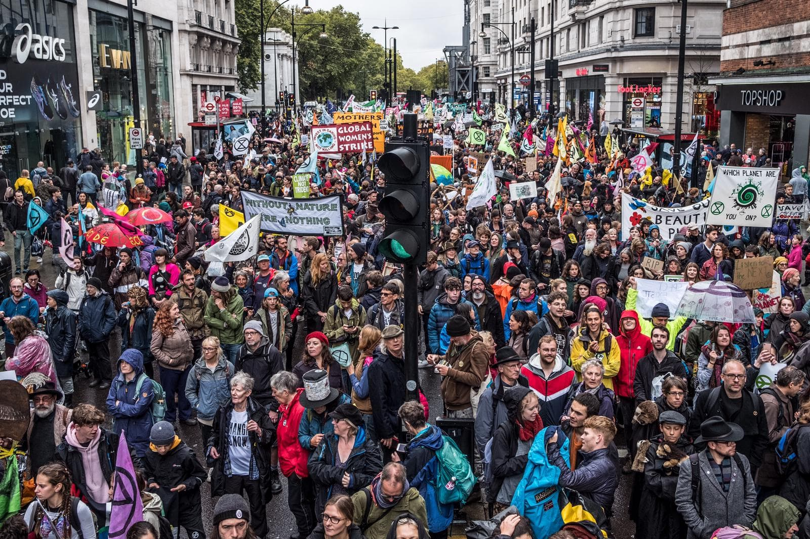 A massive march with thousands of rebels on Oxford Street in London. There are banners which read 'Global Women's Strike' and 'Without Nature We Are Nothing'.