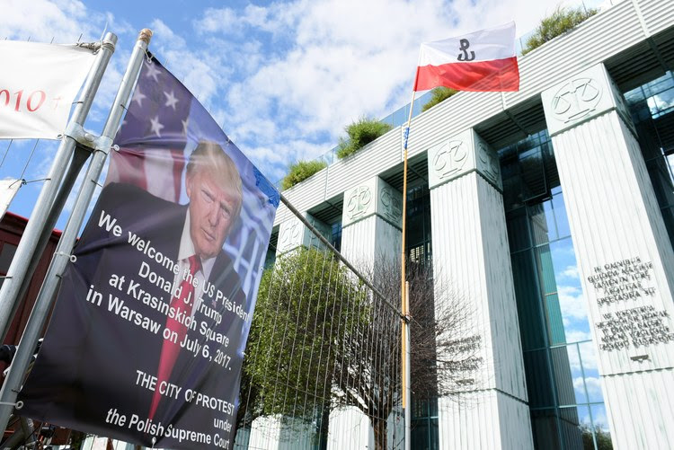 A poster of Trump hangs in Warsaw, outside the memorial where the president will speak on Thursday. (Marcin Kmiecinski/European Pressphoto Agency)</p>