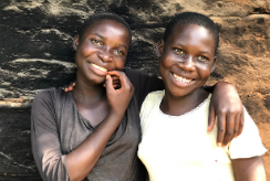 Two twin sisters embrace, standing outside their home in Uganda.
