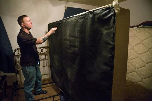 Jeremy Evans of Evans Pest Control inspects a mattress for bedbugs in Northeast Philadelphia