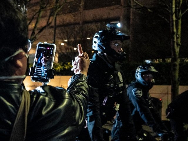 SEATTLE, WA - APRIL 12: (EDITORS NOTE: Image depicts obscene gesture) A person records police officers at a protest over the death of Daunte Wright on April 12, 2021 in Seattle, Washington. Wright, a Black man whose car was stopped in Brooklyn Center, Minnesota on Sunday reportedly for an expired …