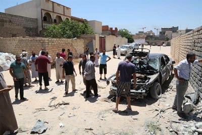 Varias personas revisan el lugar tras el impacto de unas granadas en Trípoli.