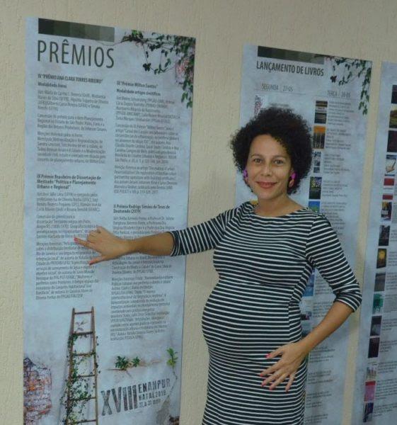 Daniele Vieira - mulher negra grávida, de cabelo curto cacheado, usando vestido listrado branco e preto - em pé, apontando para um cartaz na parede