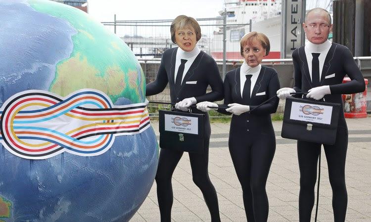 Activists dressed as Theresa May, Angela Merkel and Vladimir Putin squeeze an inflated globe during an event to protest the upcoming G20 summit. (Focke Strangmann/European Pressphoto Agency)</p>