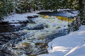 A waterfall is shown with snow along the banks of the river.