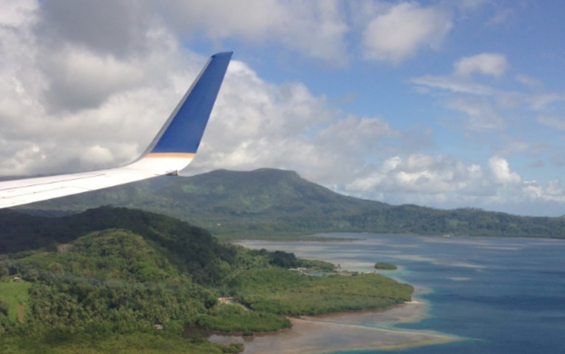 Wing of a plane, green volcanic mountains, and ocean,photo taken from plane as student landed in Micronesia