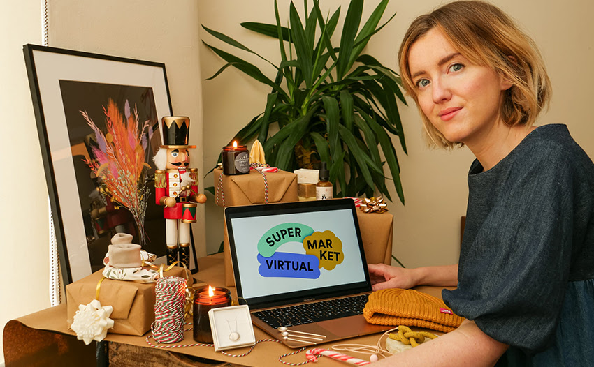 A photograph of a person sitting at a desk and looking at the camera. There is a laptop showing the Super Market Virtual logo, and several wrapped presents and christmas items on the table.