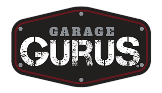 Logo of Garage Gurus. Features the word Garage in small grey stencil lettering over the word Gurus in large white stencil lettering. Both words appear on an elongated black hexagon resembling a car emblem or metal sign.