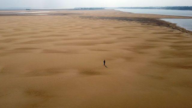 Nesta vista aérea, o ambientalista Luis Martinez caminha ao longo de um banco de areia no Rio Paraná, durante uma seca histórica perto de Paso de la Patria, Corrientes, Argentina, em 20 de agosto de 2021.