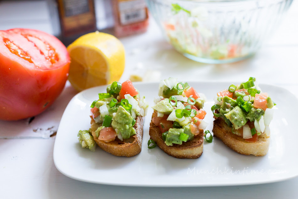 Avocado Garlic Tomato Bruschetta Recipe.  Made with toasted French bread rubbed with fresh garlic clove and topped with chopped avocados, tomatoes and onion. #BruschettaRecipe