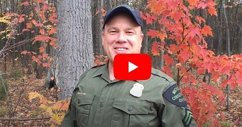Video thumbnail play button overlay on a smiling male conservation officer